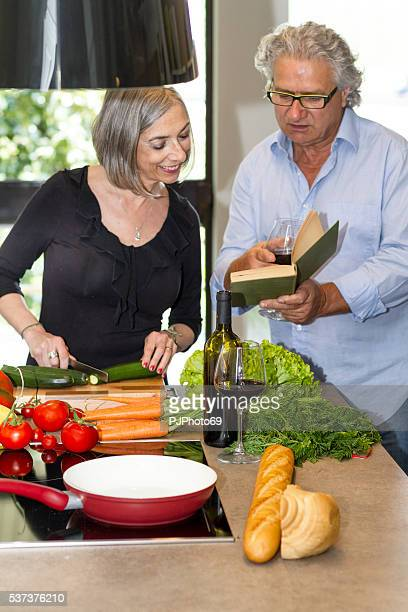 Couple of seniors cooking and reading cookbook