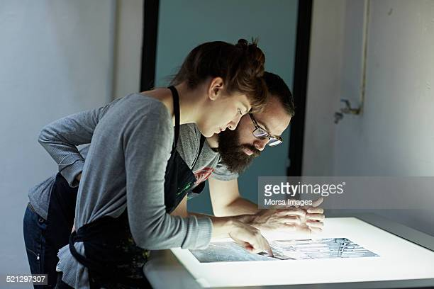 Couple of silk screen workers checking photomask