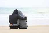 Rear view of a couple of pensive teenagers hugging and watching the sea sitting on the sand of the beach in a rainy day