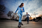 Couple of teeangers having fun in a skate park. Young woman on rollerblades and young man on skateboard behind her