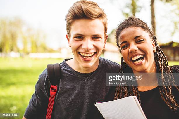 couple of teenagers student outdoors laughing