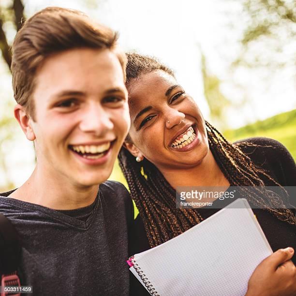 カップルの笑いのティーンエイジャースチューデント屋外