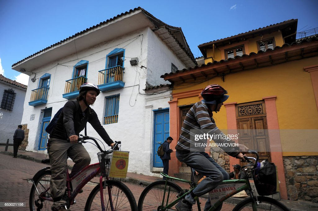 A couple of tourist bike down a street in the historic neighborhood of La Candelaria in Bogota on September 17, 2009. La Candelaria is Bogota's oldest neighbourhood and the city's historical center, known for its colonial houses with wooden balconies and clay shingle roofs. AFP PHOTO/Eitan Abramovich /