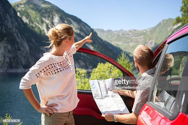 Couple of tourist with rental car reading map-Road trip