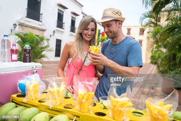 Couple of tourists eating mango in Cartagena
