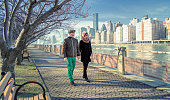 Couple of tourists in NYC walk by the Queensboro Bridge on Roosevelt Island