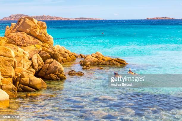 Couple of tourists snorkel in crystal turquoise water in Capriccioli beach, Arzachena Costa Smeralda, Olbia-Tempio province, Sardinia district, Italy