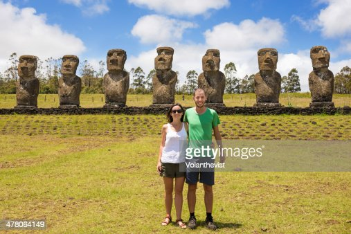 Couple of travelers with seven moai in Ahu Akivi