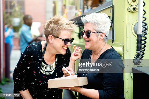 Couple of women enjoying their lunch from food truck in city street. : Stock Photo