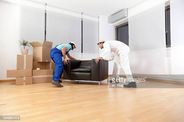Couple of workers moving the furniture into a new house