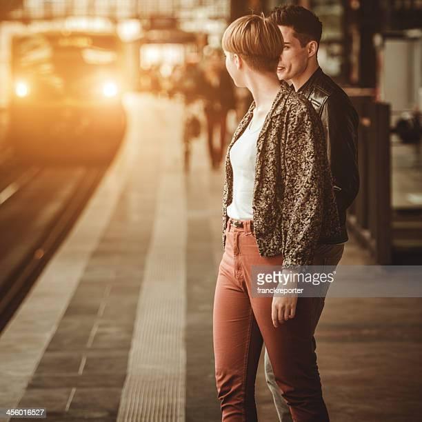 Casal de jovens adultos espera o Trem na plataforma