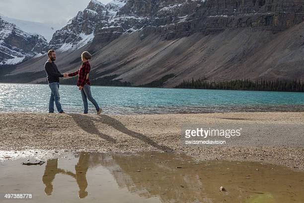 Couple of young adults holding hands by the lake