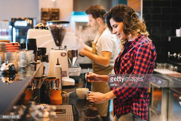 Couple of young baristas working together in a coffee shop