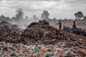 A couple of young boys walk between tons of rubbish where they work daily in the Anlong Pi landfill on June 11 2014 in Siem Reap Cambodia Dozens of...