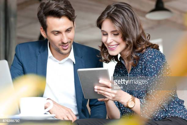 Couple of young business people looking at digital tablet