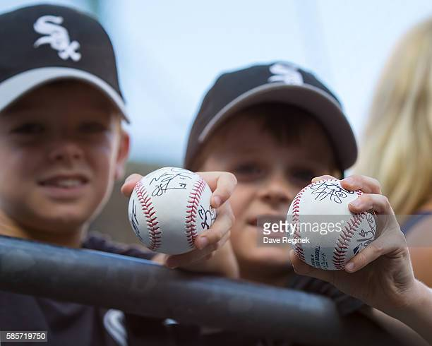 A couple of young fans hold out their autographed baseballs during a MLB game between the Detroit Tigers and the Chicago White Sox at Comerica Park...