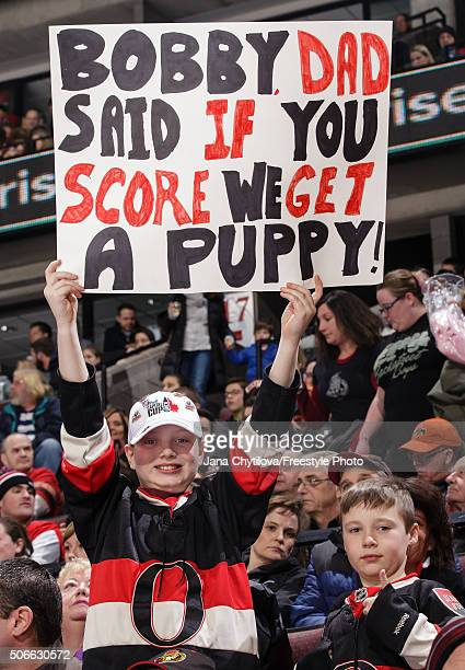 A couple of young fans hold up a sign with a promise of a puppy during an NHL game between the Ottawa Senators and the New York Rangers during an NHL...