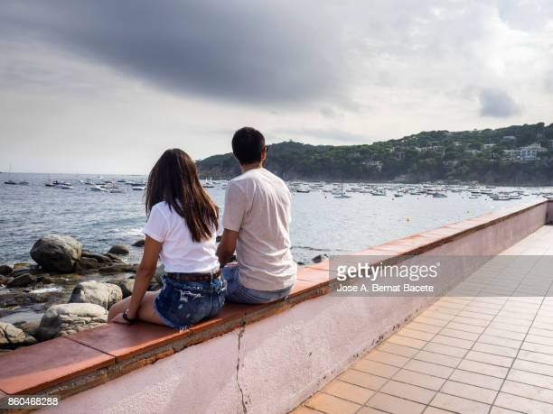 Couple of young friends sitting on a railing watching the sea. Costa Brava, Catalonia, Spain
