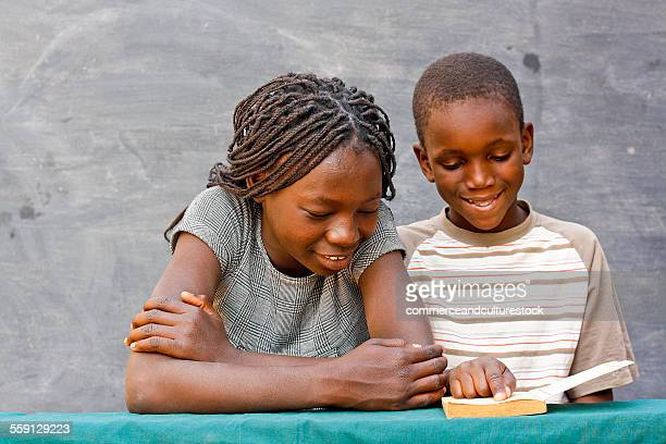 A couple of young students reading a book