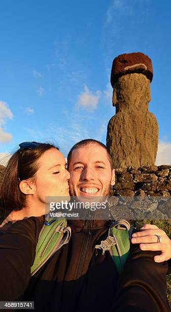 Couple of young tourists kissing in front of moai