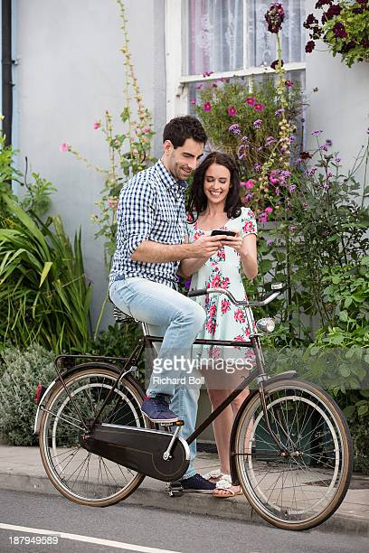 A couple on a bicycle looking at a phone