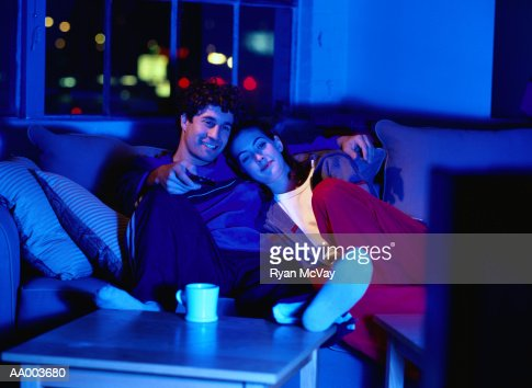 Couple on a Couch Watching Television : Stock Photo