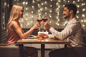 Beautiful young couple is looking at each other, clinking glasses of wine together and smiling during their date in a restaurant