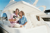 Couple on a Luxury Motorboat Thinking, the Man Holding a Brochure