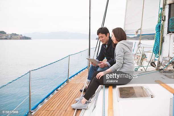Couple sur un Yacht de luxe regardant une tablette numérique