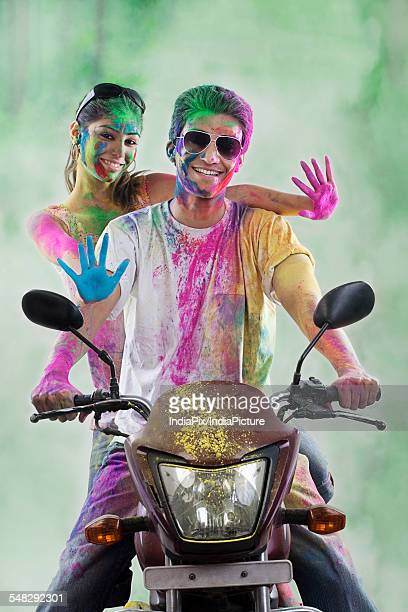 Couple on a motorcycle covered with colours