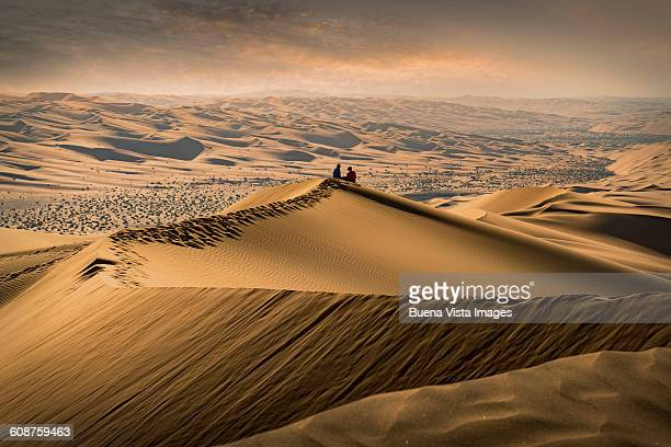 Couple on a sand dune watching sunset