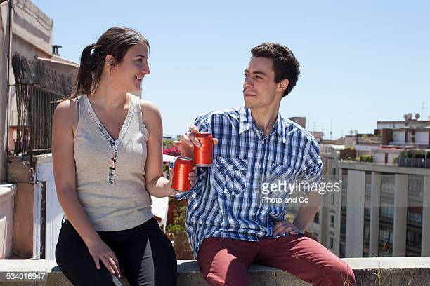 couple on a terrace drinking a beer