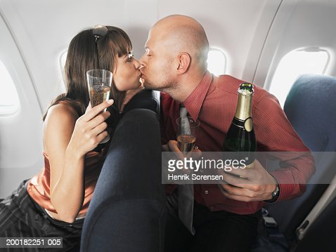 Couple on aeroplane kissing over seats, holding champagne : Stock Photo