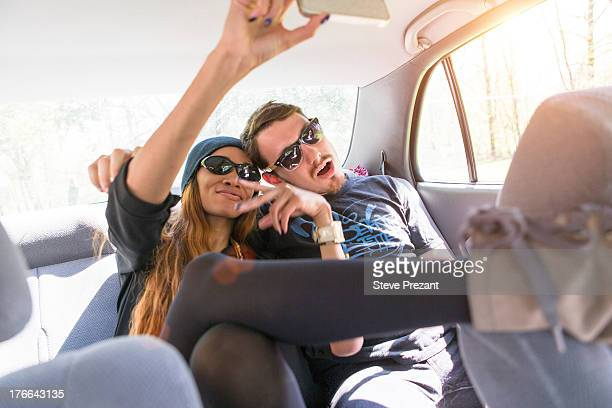 Couple on backseat in car photographing themselves