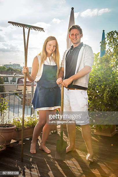 Couple On Balcony with Garden Rake And Spade, Munich, Bavaria, Germany, Europe