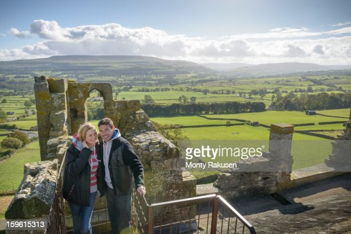 Couple on battlements of Bolton Castle with views of Wensleydale, high angle. A 14th century Grade 1 listed building, Scheduled Ancient Monument : Stock Photo