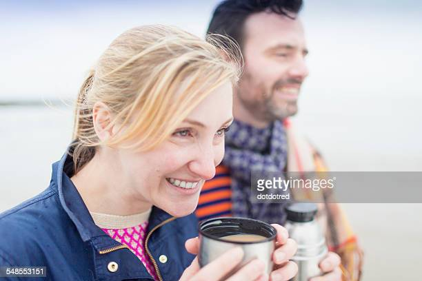 Couple on beach, drinking hot drink from drinks flask