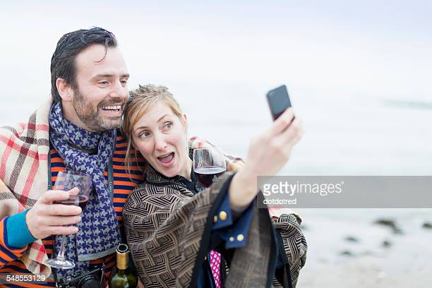 Couple on beach, drinking wine, taking self portrait using smartphone