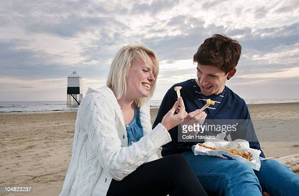 Couple on beach eating fish and chips