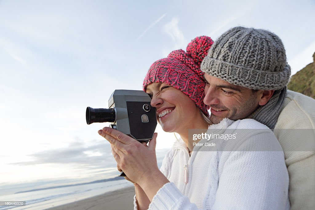 Couple on beach in winter with video recorder : Stock Photo