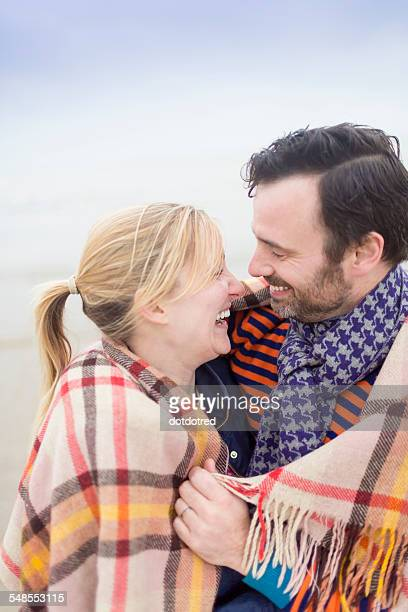 Couple on beach, laughing and keeping warm under blanket