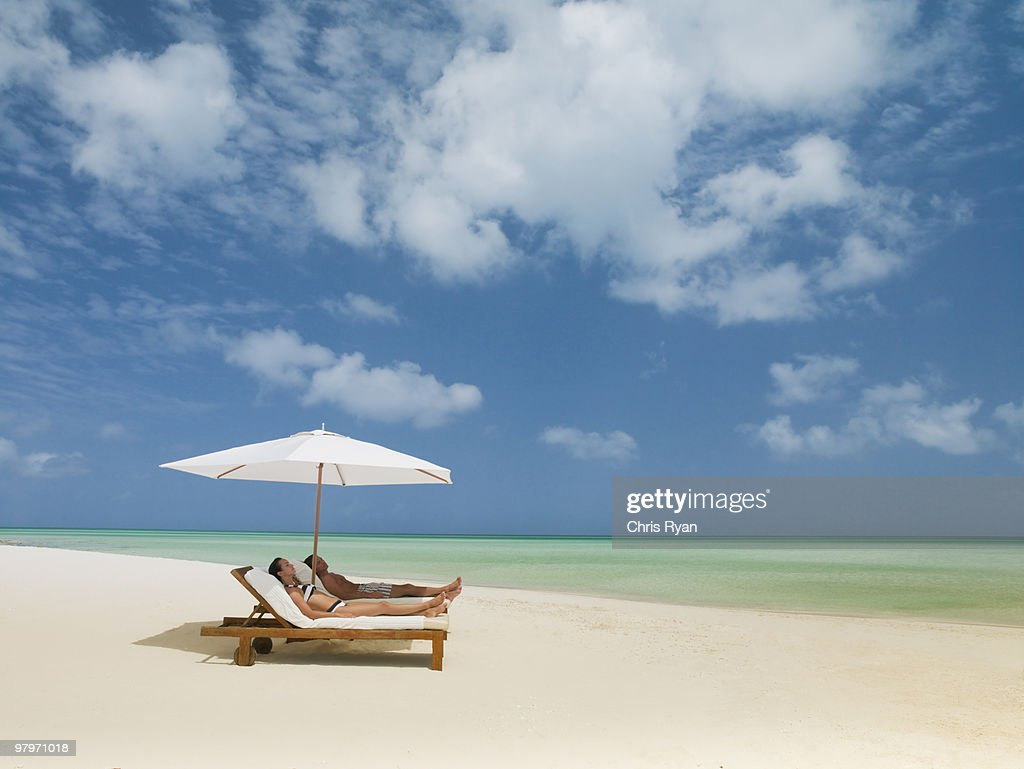 Couple on beach laying on lounge chairs under beach umbrella : Stock Photo