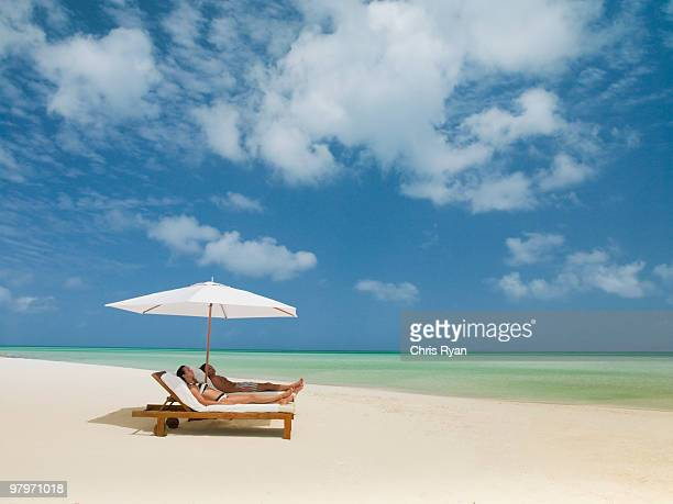 Couple on beach laying on lounge chairs under beach umbrella
