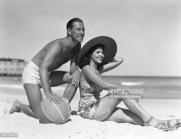 Couple on beach, man leaning on ball, woman sitting look out to ocean, wearing sun hat.