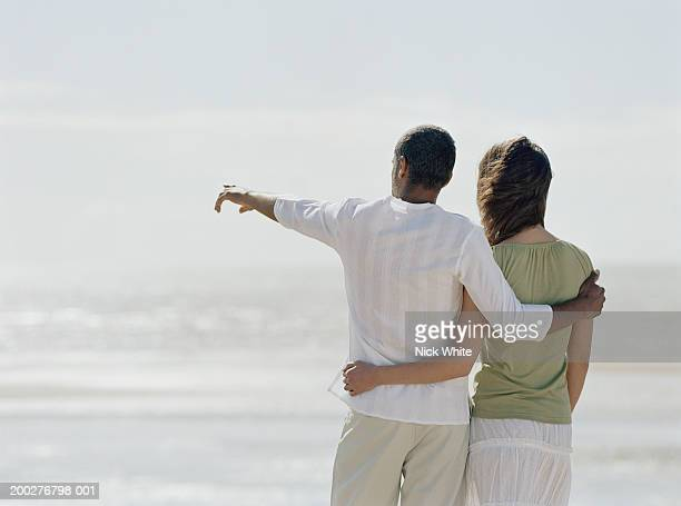 Couple on beach, man pointing to sea, rear view