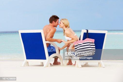 Casal na praia relaxante nas Cadeiras : Foto de stock