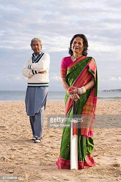 Couple on beach with cricket set