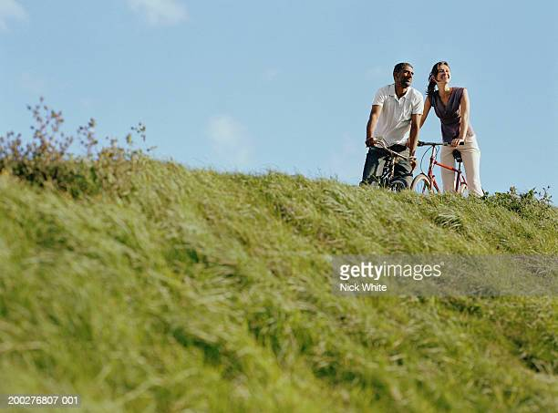 Couple on bicycles at top of grassy bank, low angle view