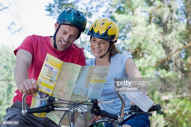 Couple on bicycles looking at map