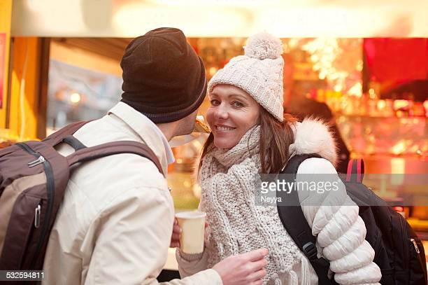 Pärchen auf dem Weihnachtsmarkt in Ljubljana trinkt Punch